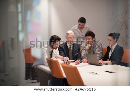 Young business people group on meeting at modern startup office with  senior manager.  Team leader looking presentation and  results  on tablet and laptop computer. - stock photo