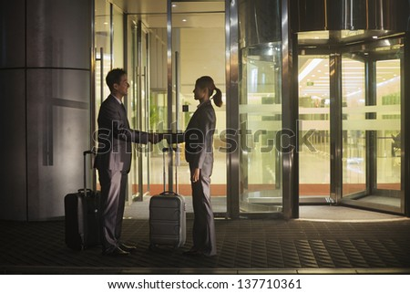 Young business people handshaking outside of the office - stock photo