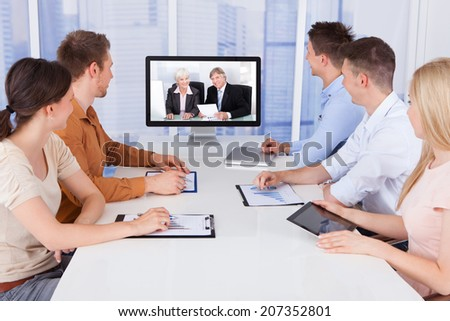Young business people looking at computer monitors in conference room - stock photo