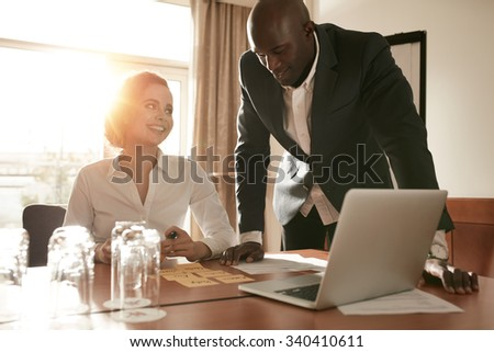 Young business people meeting in conference room of a hotel. African businessman with caucasian businesswoman at conference table discussing new project plan. - stock photo