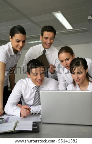 Young business people meeting in front of a laptop computer - stock photo