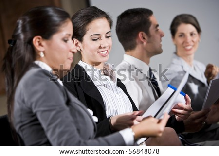 Young business people or college students sitting in row reading report in presentation - stock photo