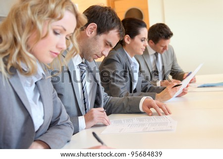 Young business people signing application form - stock photo