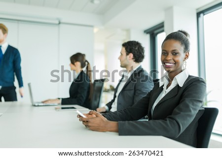 Young business people sitting at a conference table while listening to the lecturer  and learning new technologies and having a laugh - stock photo