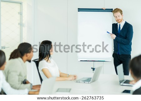 Young business people sitting at a conference table while listening to the lecturer pointing at the whiteboard - stock photo