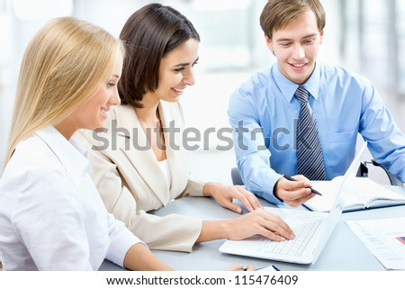 Young business people sitting at desk, using computer at business training, smiling. - stock photo