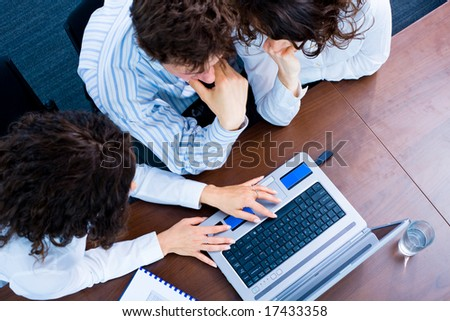 Young business people sitting by table at office, working together on laptop computer. High-angle view. - stock photo