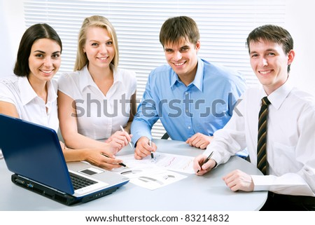 Young business people smiling looking at camera