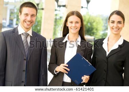 Young business people standing against a building of office - stock photo
