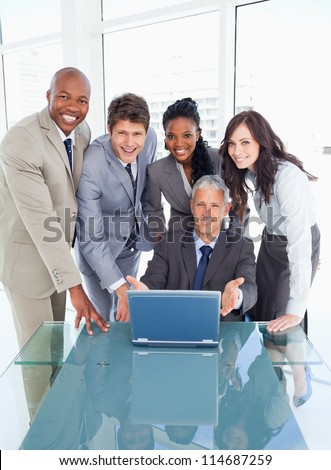 Young business people standing behind their director proudly showing the laptop - stock photo
