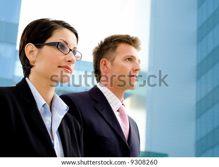 Young business people standing in front of a modern office building. - stock photo