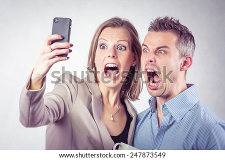 Young business people taking selfie with a smartphone and making funny grimaces in the office - stock photo