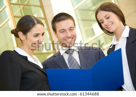 Young business people talk against a building of modern office - stock photo
