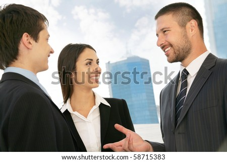 Young business people talking against a building of modern office - stock photo