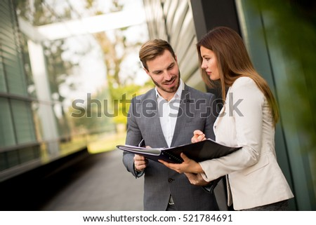 Young business people talking and viewing documents outdoor