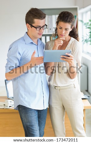 Young business people using tablet PC while standing in office - stock photo
