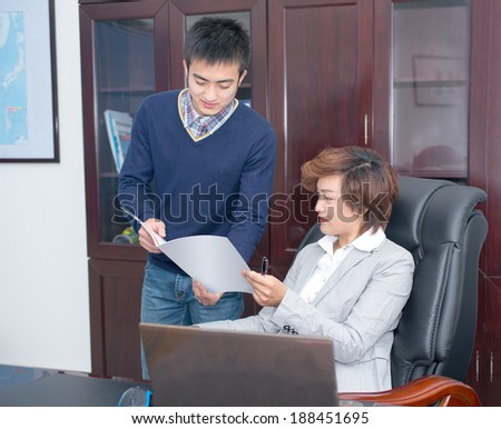 Young business people with the boss to discuss the file - stock photo