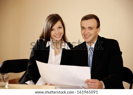 Young business people woking with diagram and looking at camera in the office - stock photo
