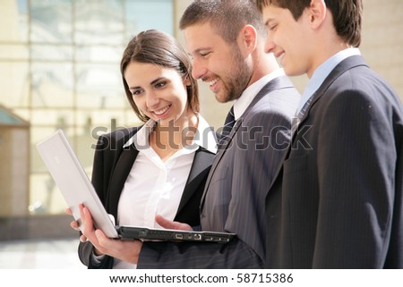 Young business people work on the laptop against a building of modern office - stock photo