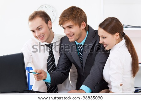 young business people working in team together on laptop computer, men and women discussing the problem point finger on screen happy smile, businesspeople sitting at desk office