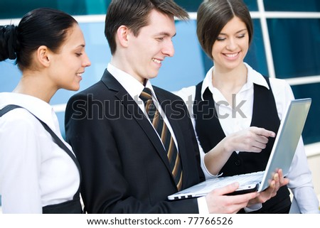Young business people working on laptop in modern office building