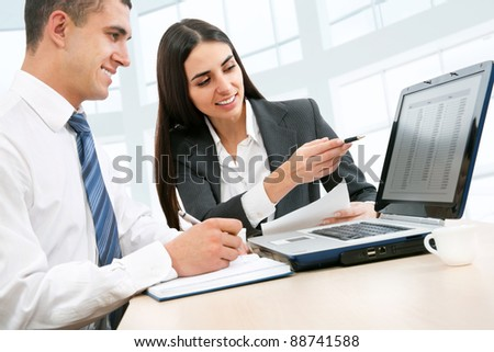 Young business people working over a laptop computer