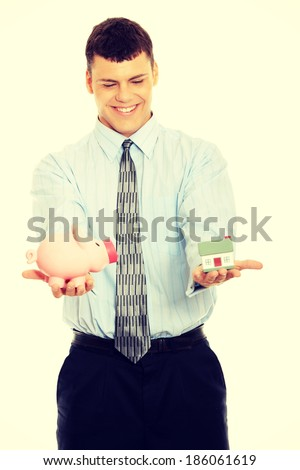Young business person encourage saving money. Holding house model and piggy bank