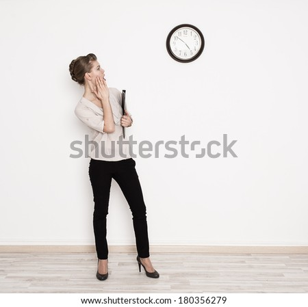 Young business person standing at office and looking at time in urgency. - stock photo