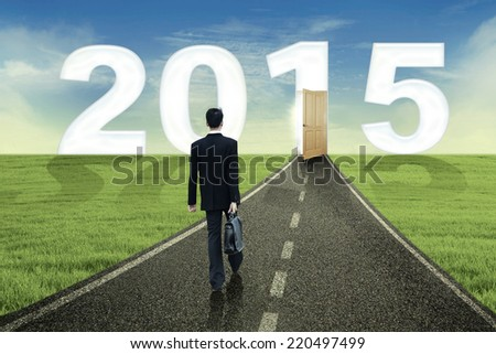 Young business person walking towards the future to success in 2015 - stock photo