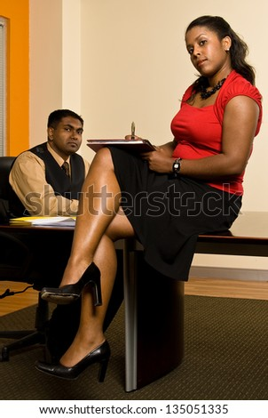 Young business professional giving his secretary direction as she takes notes. - stock photo