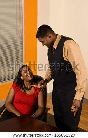 Young business professional offering his secretary a cigar. - stock photo