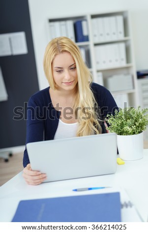 Young business secretary or personal assistant sitting at her desk in the office working on a laptop computer with a serious expression - stock photo