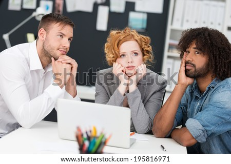 Young business team at a loss for a solution sitting at a table with serous expression deep in contemplation as they seek an answer - stock photo