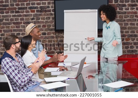 Young business team clapping hands in meeting at the office - stock photo
