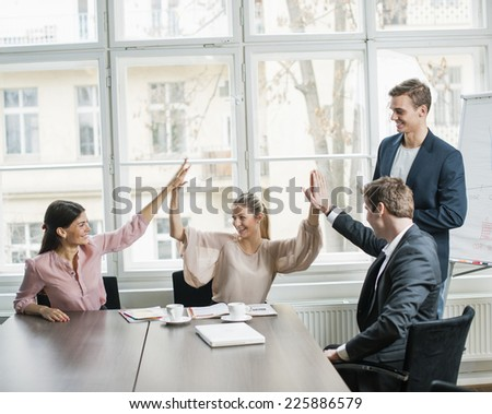 Young business team doing high five at conference table - stock photo