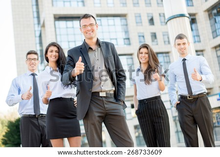 Young business team, elegantly dressed standing outside in front of office building with thumbs up. Looking at camera. - stock photo
