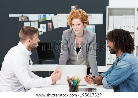 Young business team having a brainstorming session gathered around a desk and computer in the office - stock photo