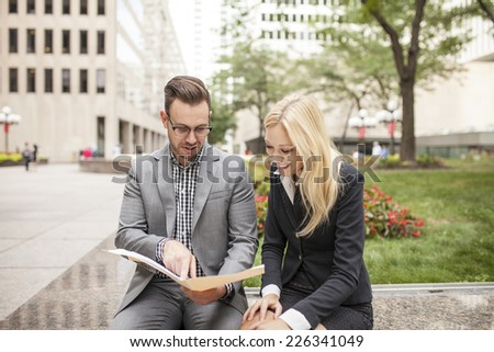 Young business team outdoors in urban setting with woman in charge displaying power - stock photo