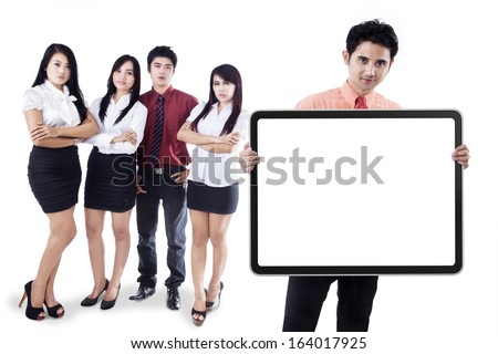 Young business team showing an empty banner isolated on white background - stock photo