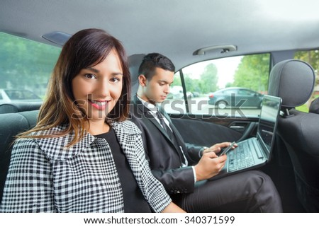 Young business team sitting on the backseat of a taxi while traveling to work - stock photo