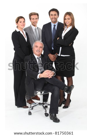 Young business team standing behind their boss - stock photo