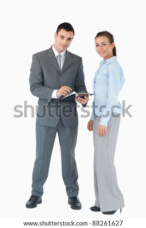 Young business team with clipboard against a white background