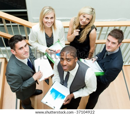 Young business team working on stairs and smiling at the camera - stock photo