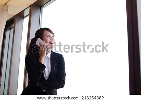 Young business travel woman speaking smart phone in her hotel room, asian - stock photo