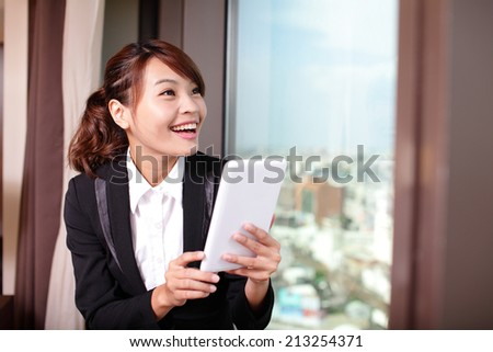 Young business travel woman using digital tablet and smart phone in her hotel room, asian - stock photo