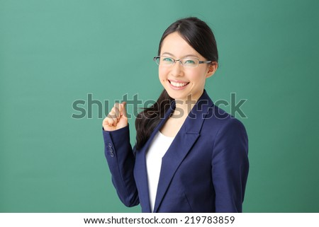 young business woman against green background - stock photo