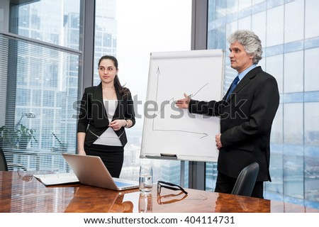 Young business woman and mature business man making a presentation - stock photo