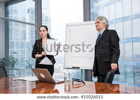 Young business woman and mature man making a presentation - stock photo
