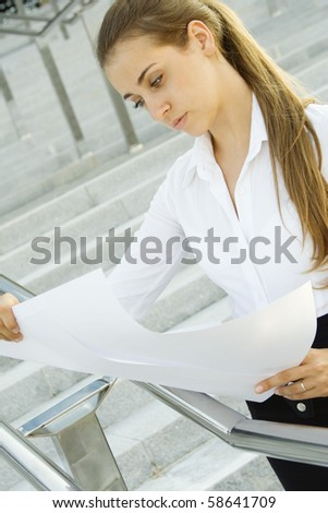 Young business woman architect / engineer plans. Reads - stock photo