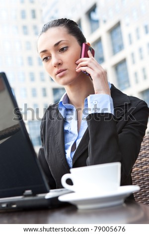 young business woman calling by telephone, working on laptop, outdoor - stock photo
